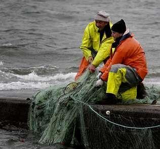Dos marineros tratan de recuperar los aparejos en el puerto de Tragove.