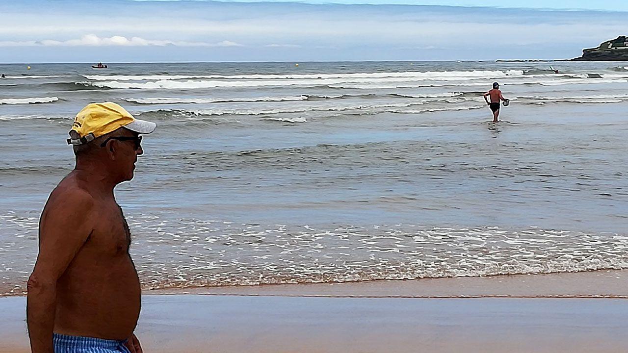 Rodri Rios Cultural Real Oviedo Reino de Leon.Un paseante y un bañista en la apertura de la temporada oficial de baños en la playa de San Lorenzo