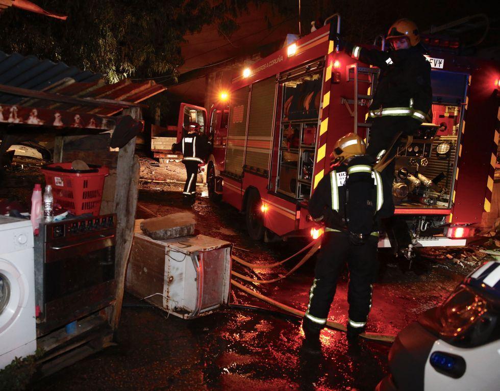 Los bomberos, durante las labores de extinción del fuego.