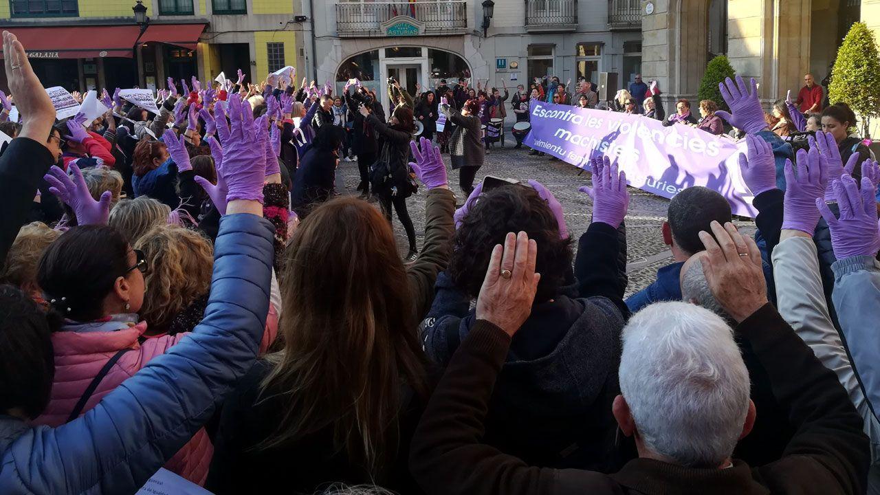 Manifestantes alzan las manos en la concentración feminista de la Plaza Mayor gijonesa