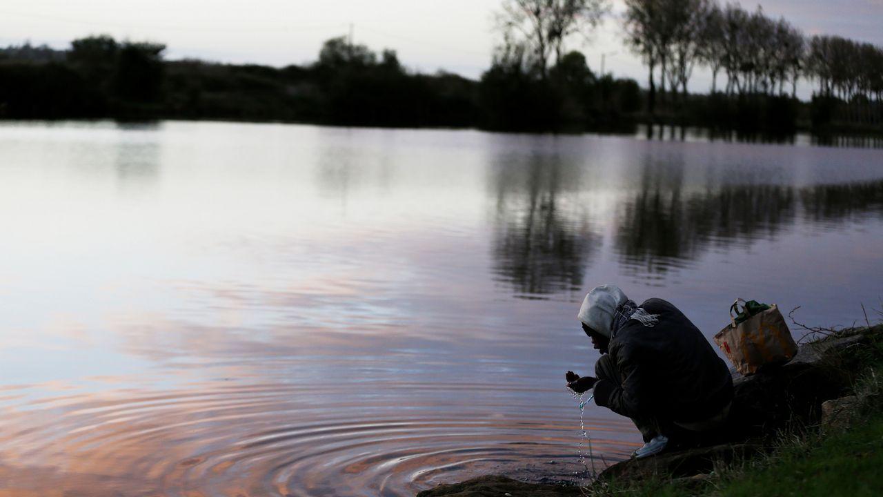 .Un emigrante se cepilla los dientes junto a una fuente de agua cerca del puerto de Oustreham, cerca de Caen, en el noroeste de Francia