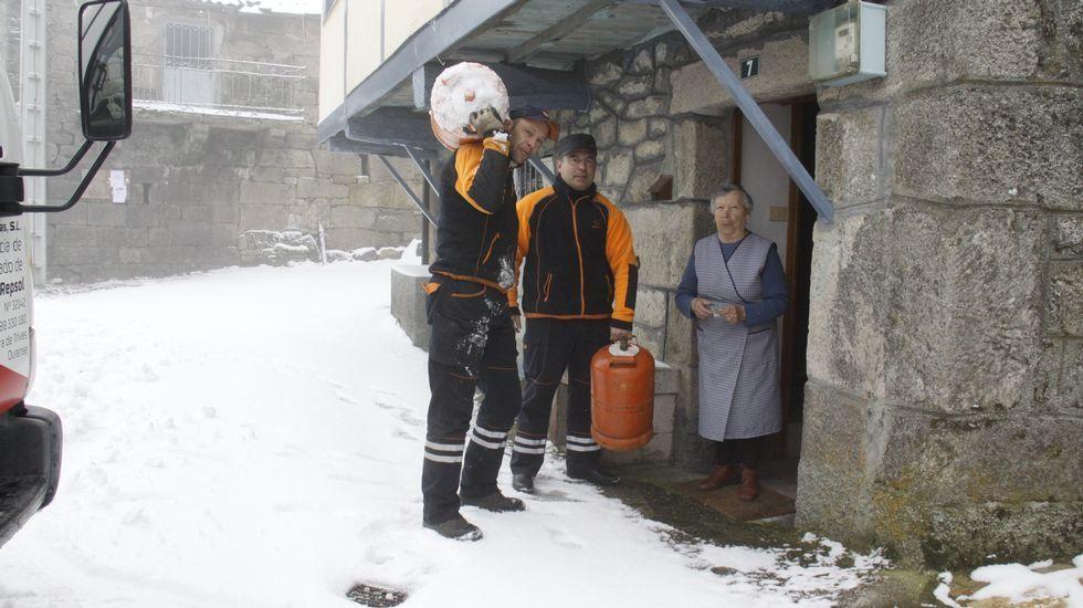 Butaneros de Trives abren las pistas llenas de nieve para hacer el reparto.Aqualia reparte garrafas de agua en su oficina de Ribadavia