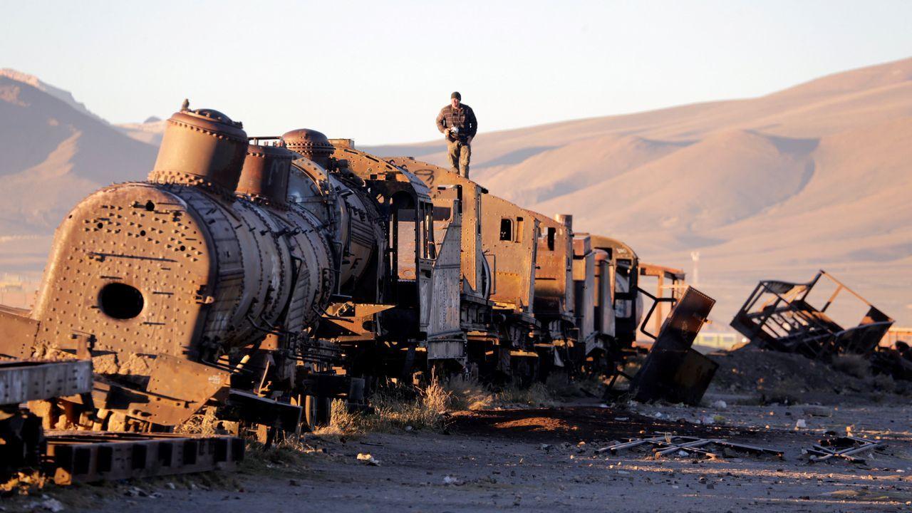 Un hombre camina sobre un viejo tren de la compañía ferroviaria de Bolivia, en un cementerio de trenes en Uyuni (Potosí)