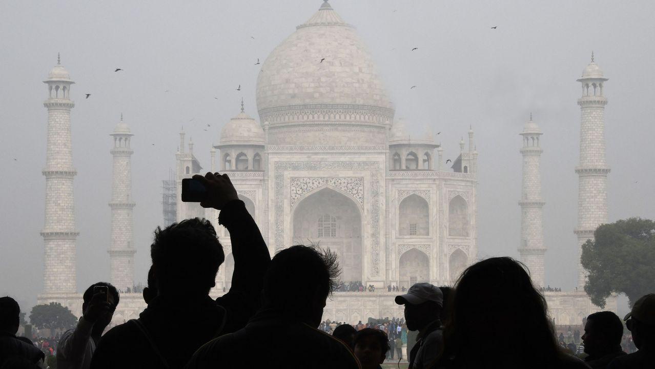 Visitantes toman fotos ante el Taj Mahal, en India