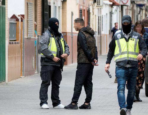 Dos agentes de la policía caminan y hablan con algunas personas durante el registro de la casa en Sevilla del presunto yihadista