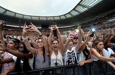 Jóvenes sacando fotos y vídeos con sus móviles en un concierto de Rihanna en París.