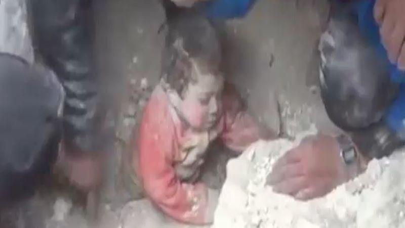 Una niña es rescatada de entre los escombros tras un bombardeo en Alepo.Dos hombres evacúan a dos niños en un edifico alcanzado por barriles bomba en Alepo.