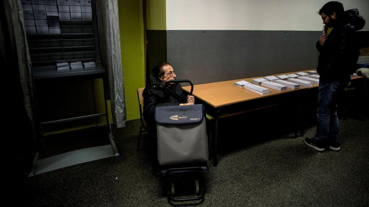 .Dos personas esperan en la zona de papeletas del colegio Joan Miró de Barcelona