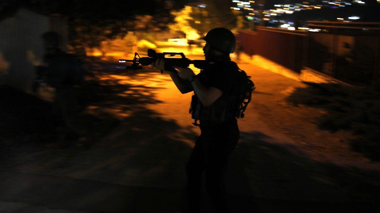 Un soldado israelí se mantiene alerta cerca de las casas en el asentamiento de Rechelim en Cisjordania durante un simulacro del ejército durante toda la noche que simula un ataque dentro de un asentamiento israelí