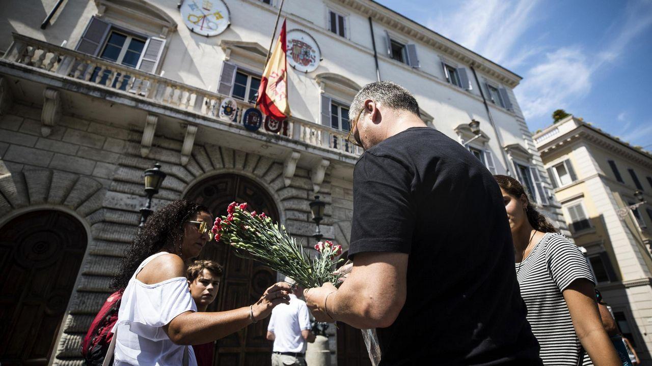 .Varias personas prepararan flores para colocarlas en la puerta de la embajada española en la Santa Sede en Roma