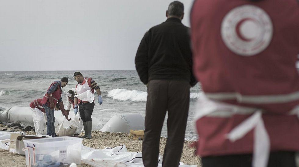 Tragedia en la costa libia.Una voluntaria de la ONG MOAS sostiene en sus brazos a dos pequeños rescatados del mar Mediterráneo