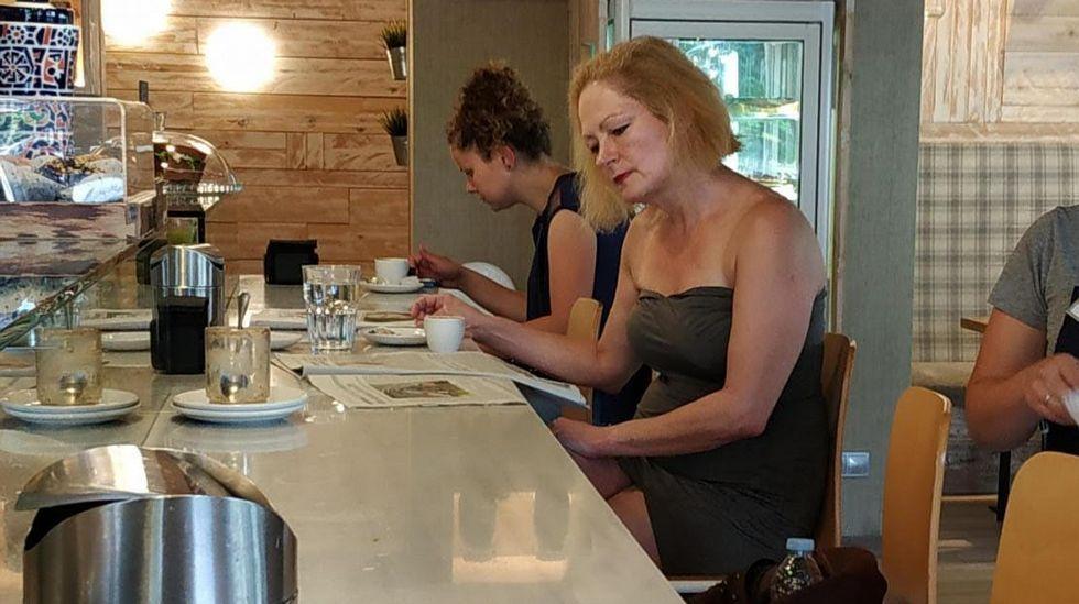 La jueza, desayunando esta mañana y leyendo el periódico con la noticia de su suspensión temporal, en una cafetería cercana a la consulta de tarot que le costó la sanción