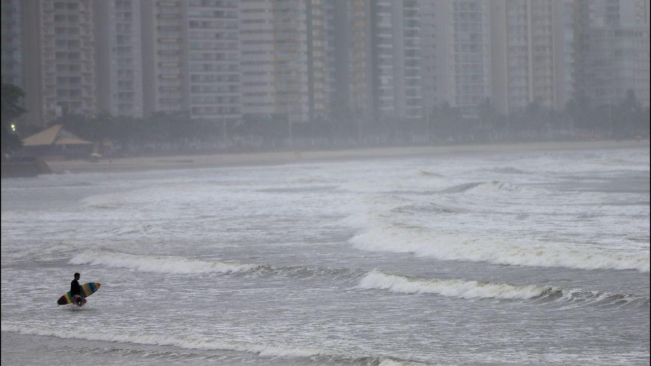 Un surfista se prepara para entrar en el mar durante lluvia, en Sao Paulo