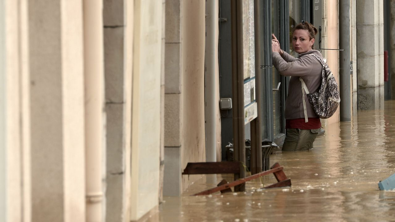 Una joven se agarra a unos barrotes durante una riada en el sur de Francia