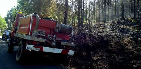 Un camión cisterna del Ayuntamiento, junto a los restos humeantes del último incendio