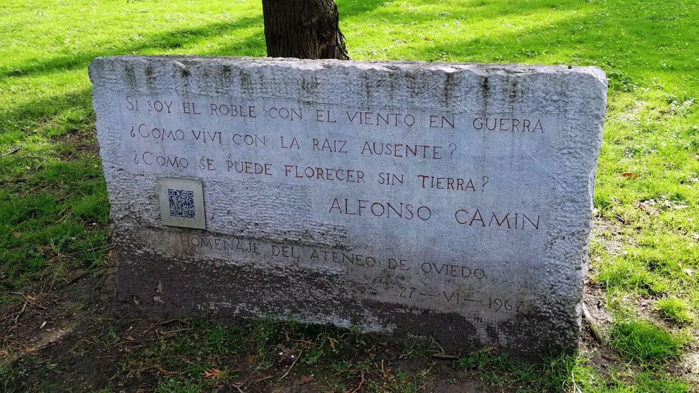 La «fiesta verde» clama en Oviedo contra el cambio climático.La placa homenaje al poeta Alfonso Camín, junto a la fuente de El Angelín