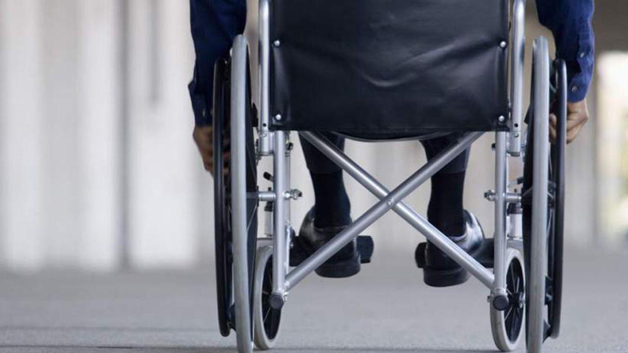 Bebé pie mano.Un persona en una silla de ruedas