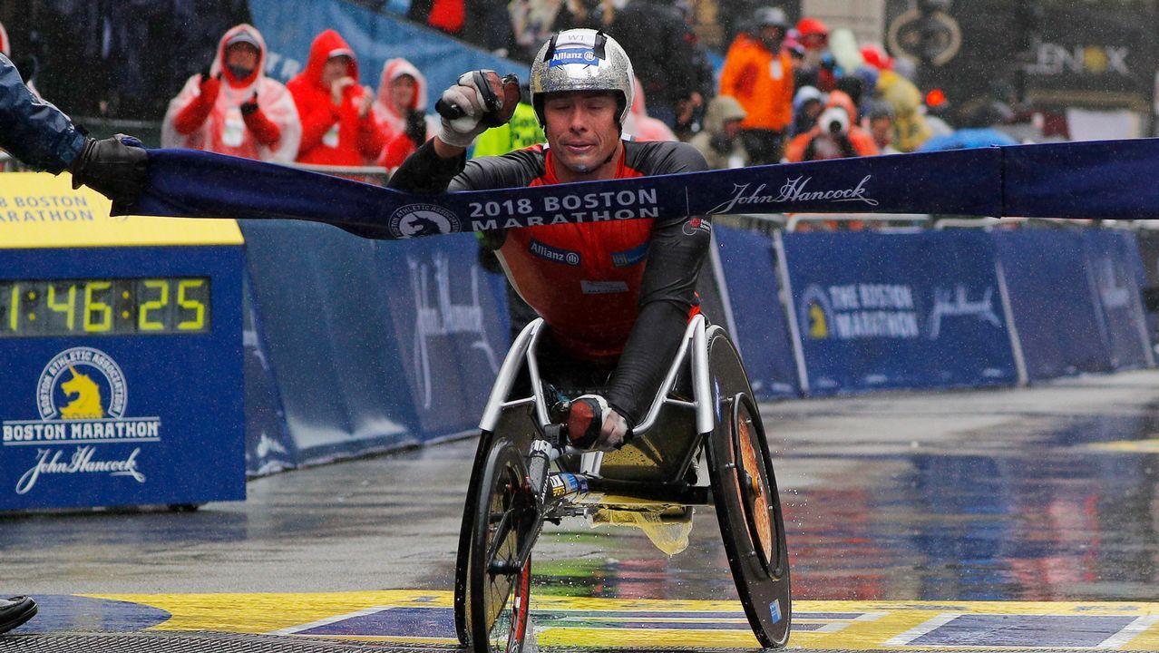 El atleta Marcel Hug cruza la línea de meta en la maratón de Boston