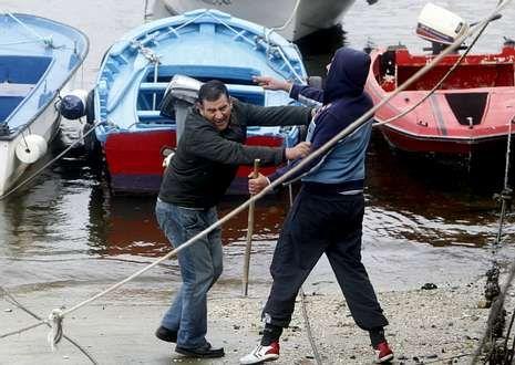 Escrache de los futbolistas del Ourense contra su directiva.Algunos de los «lazaretos» tiraron piedras a la lancha de vigilancia en cuanto asomó.