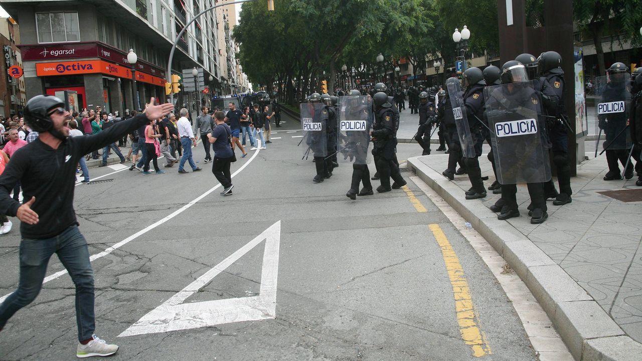 Agentes de la Policía Nacional forman un cordón policial en el exterior de un instituto en Tarragona.