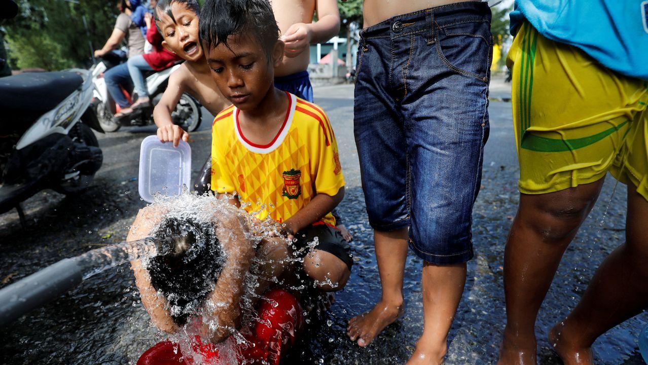 Un grupo de niños usa una tubería de agua para bañarse en un campamento para personas desplazadas por un terremoto y un tsunami en Palu, Indonesia