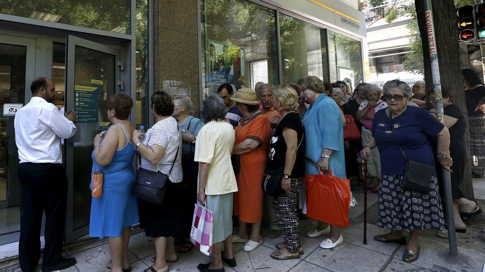 Una pensionista forcejea para entrar a una sucursal bancaria en la isla de Creta.