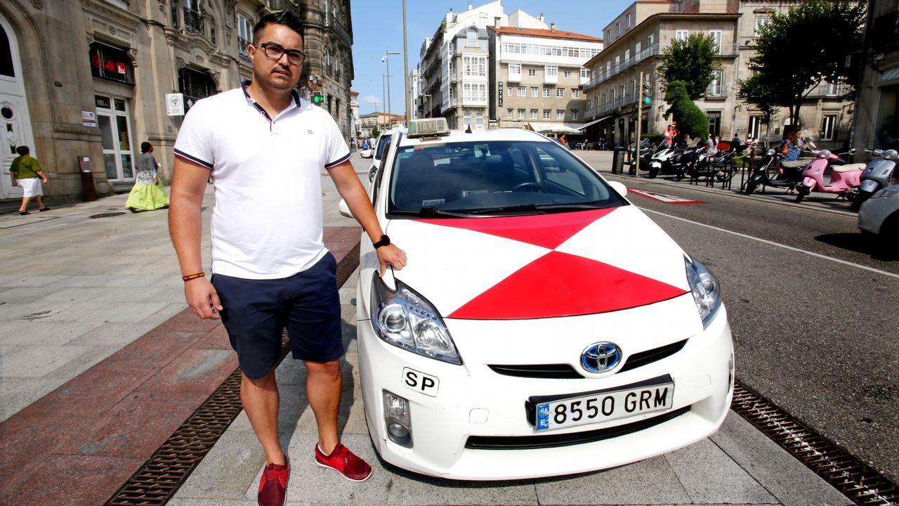 El taxista Daniel Matías posa al lado de su vehículo en el centro de Vigo