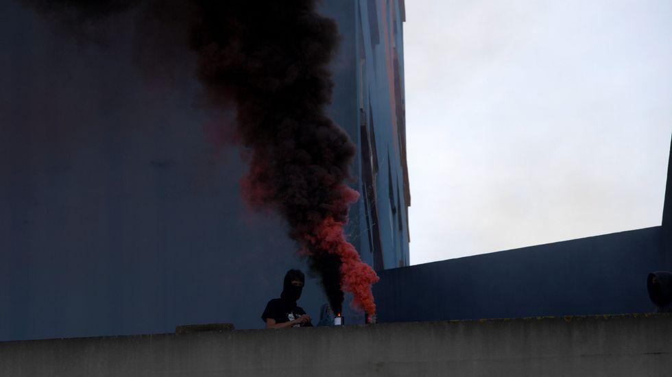 Un joven con la cara tapada explota un bote de humo, durante la manifestación de CSI, SUATEA, CNY y CGT, por el Primero de Mayo, en Gijón