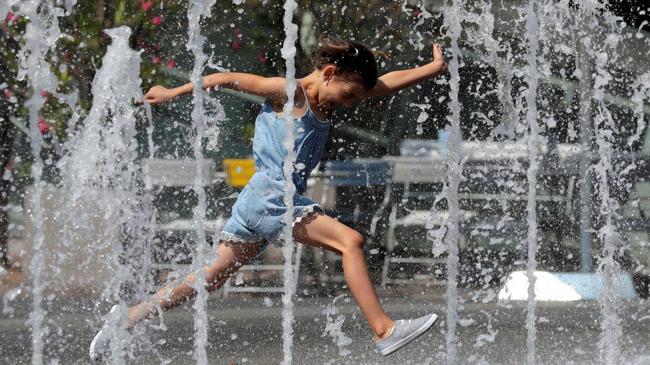 Una niña salta en una fuente de agua en el centro de Viena