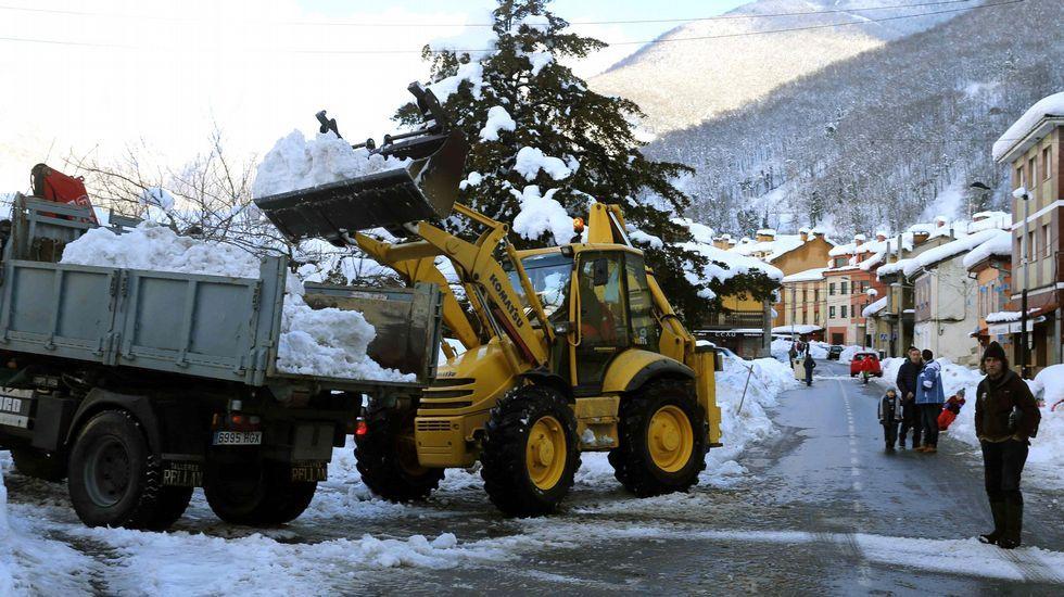 Un hombre muestra el espesor de la nevada en Riofrío, en la vertiente asturiana de San Isidro.Una máquina excavadora retira nieve en Felechosa