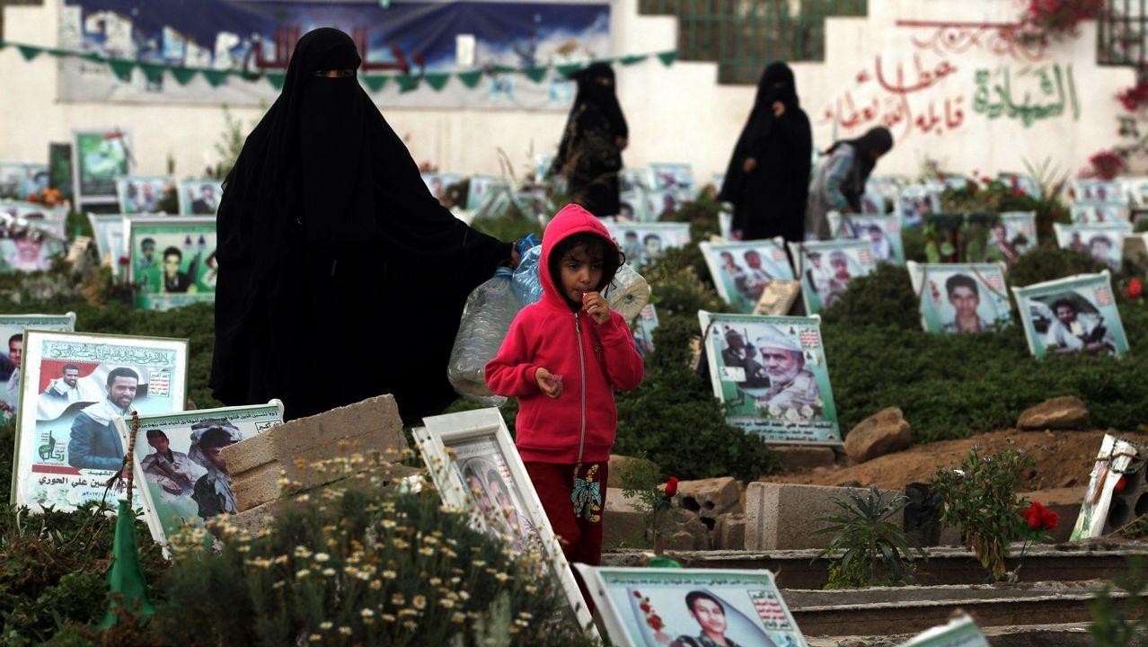 Una madre y su hija pasean junto a las tumbas de ciudadanos muertos durante la guerra en Yemen