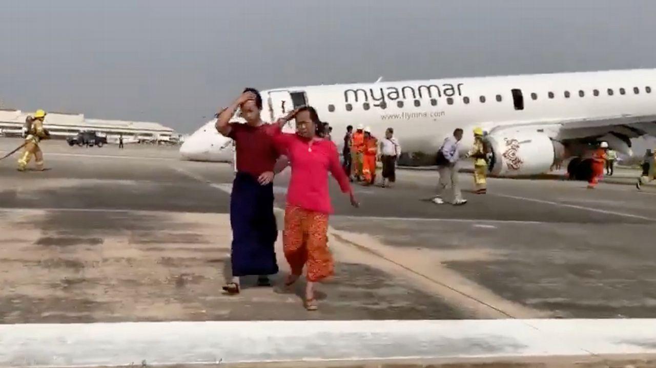 Picnic de los trabajadores del aeropuerto en protesta por el cierre de la cantina.Dos mujeres abandonan el avión sinistrado mientras operan los servicios de emergencias.