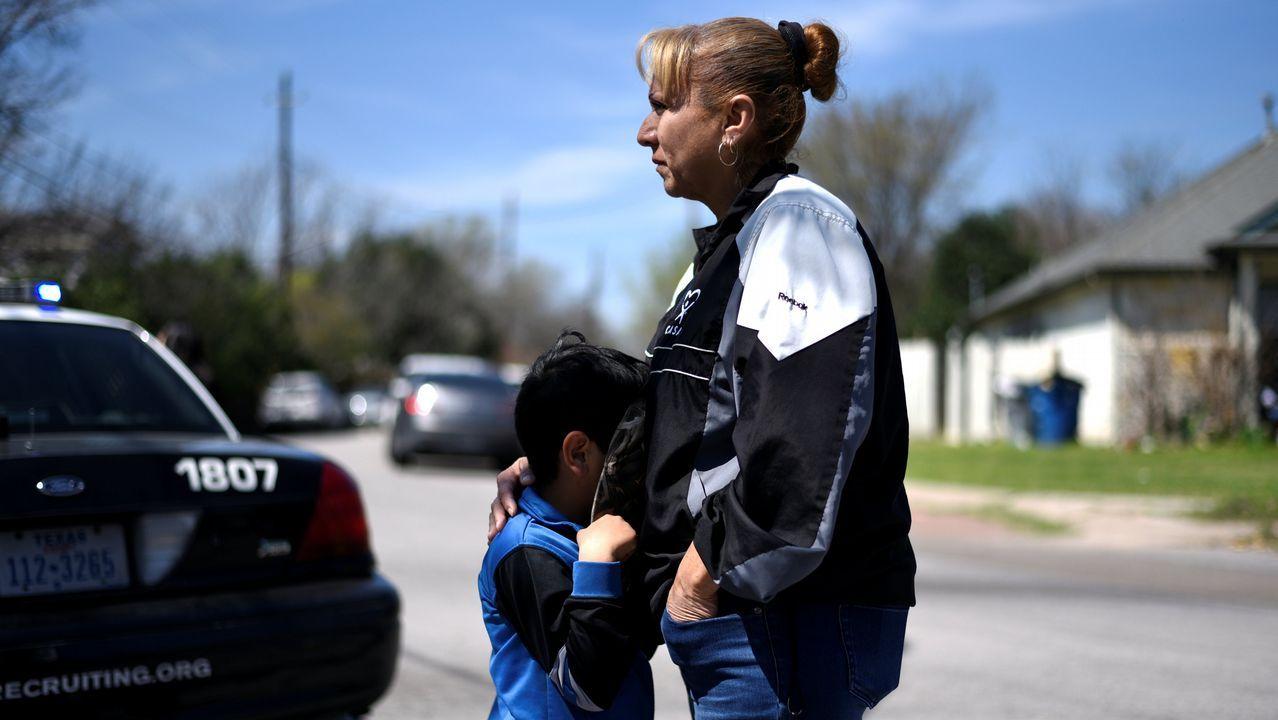 Un niño oculta el rostro contra el cuerpo de su madre en el vecindiario donde se produjo la tercera explosición, en Austin