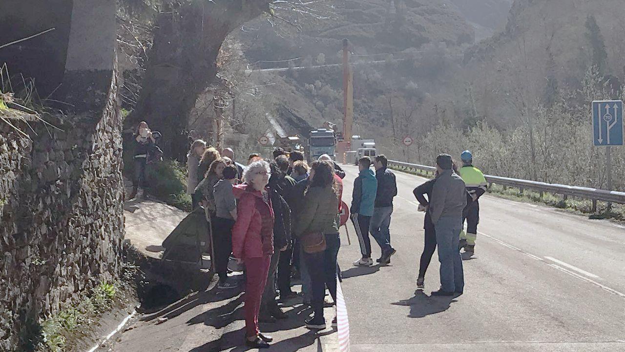 Un camión se dirige hacia el argayo que bloquea la carretera de Caso y que está siendo retirado.Concentración de protesta en el argayo que mantiene cortada la AS-17 y el acceso a Caso