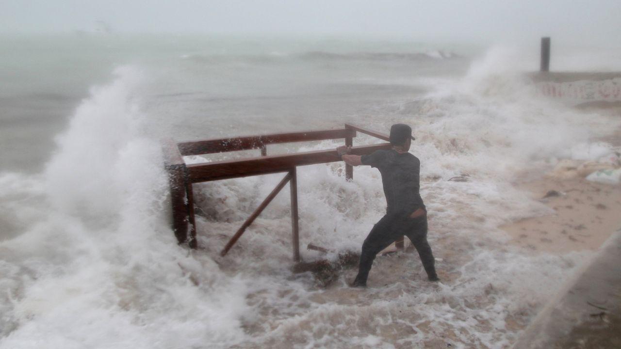 La lluvia une a Galicia con Noruega.Un hombre trata de recuperar del mar una de las mesas de su restaurante que se ha llevado el mar tras el devastador paso del huracán «María»