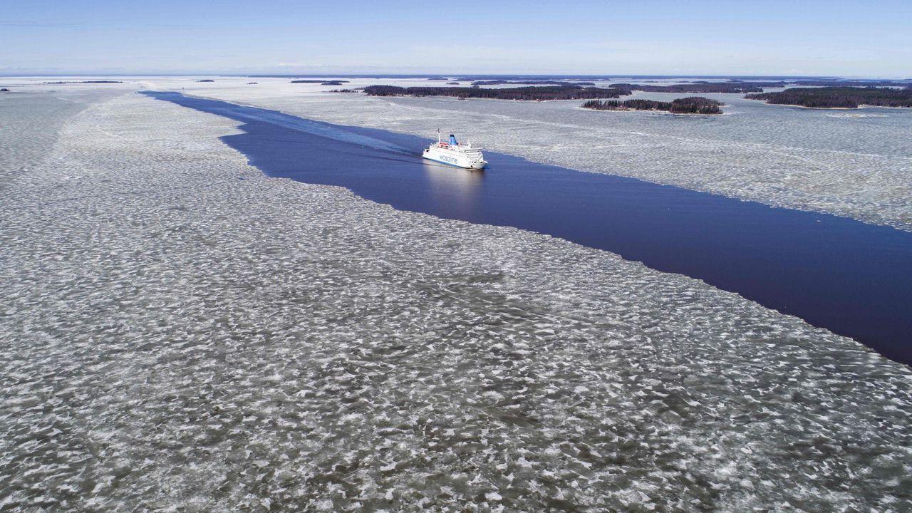 .Vista aérea en la que se ve un ferry navegando a través del hielo derretido en el canal principal entre las islas del archipiélago Merenkurkku, en el oeste de Finlandia