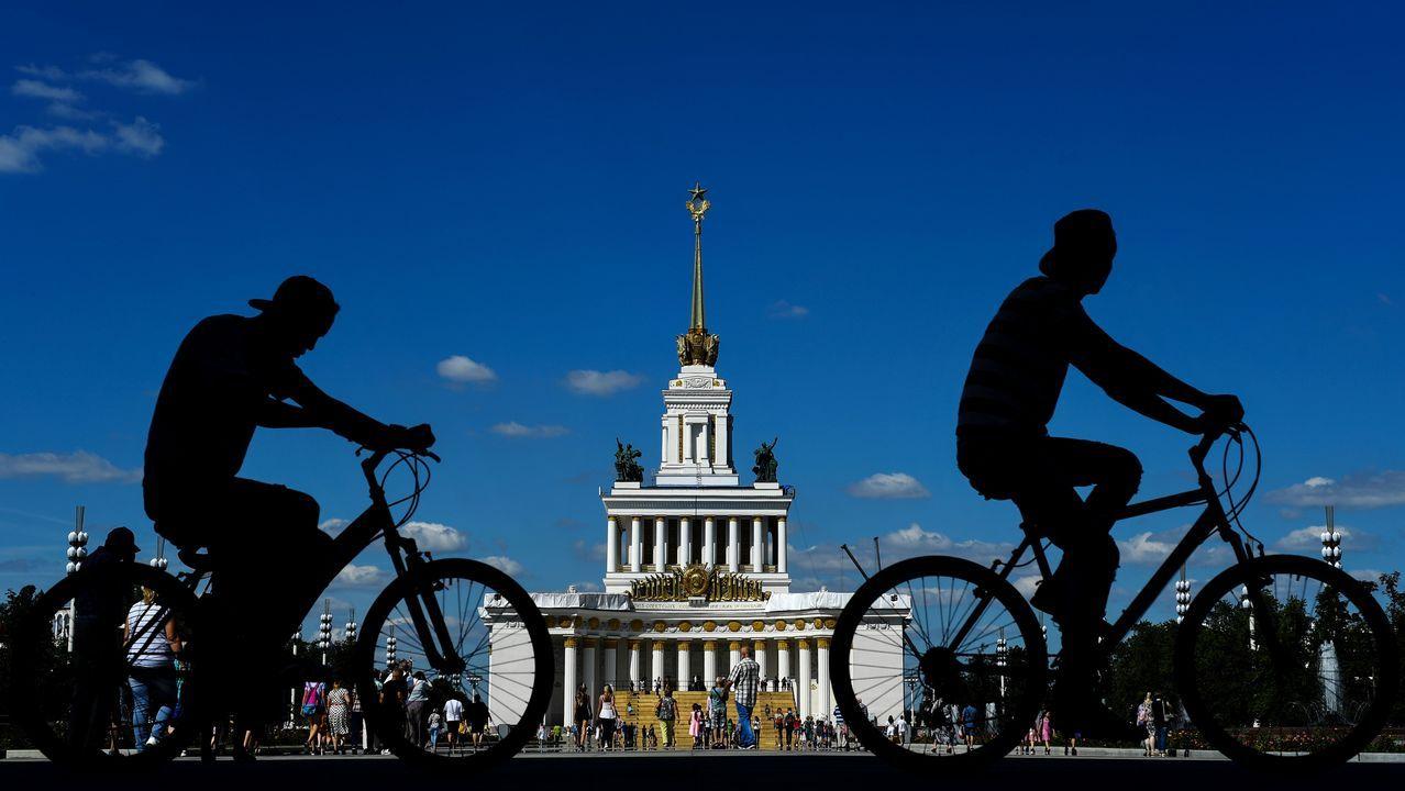 Hombres andan en bicicleta por un callejón del Centro de Exposiciones de Rusia (VDNKh), una feria comercial y parque de atracciones, en Moscú