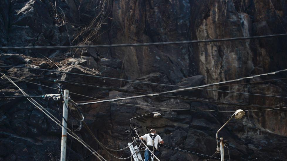 Un hombre trabaja en el tendido eléctrico dañado por el fuego en Funchal, la capital de Madeira