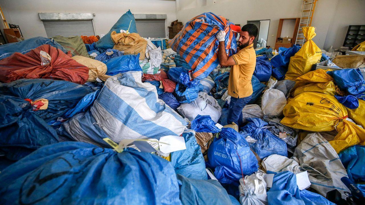Un empleado postal palestino revisa sacos de correo no entregados que datan de 2010, que Israel ha retenido en la oficina central de intercambio internacional en la ciudad cisjordana de Jericó. Israel había retenido la mercancía durante años, pero se lo entregó a las autoridades palestinas después de un acuerdo.