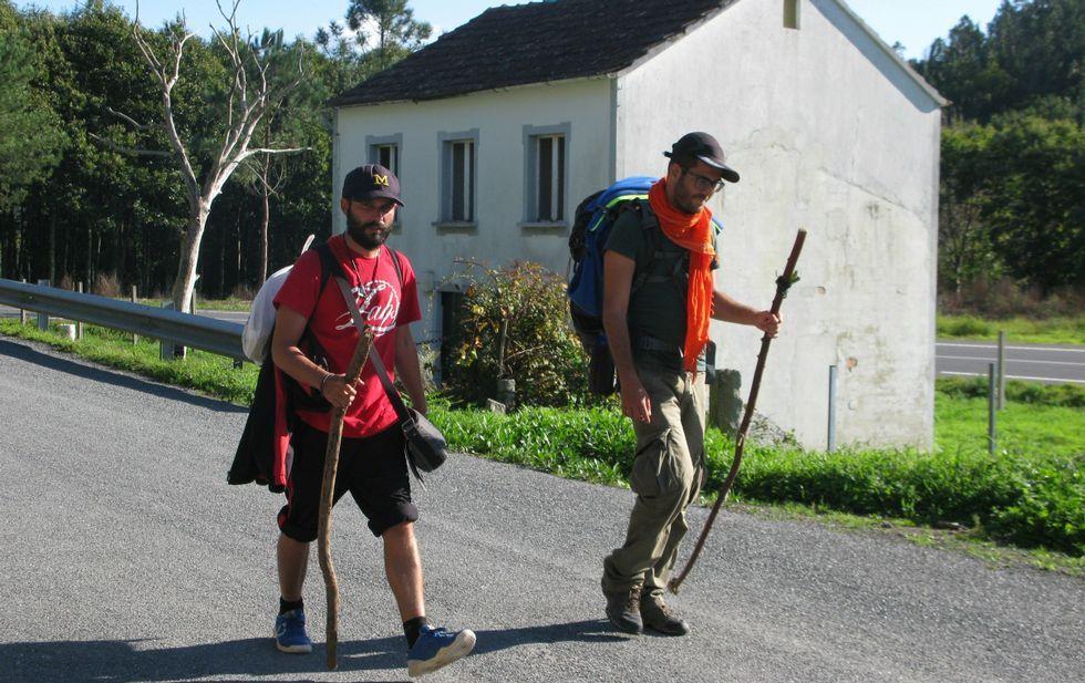 Sendero por el río Sarela y Camino de Fisterra.Dos peregrinos pasan ante la casa que el Concello de Negreira quiere para servicio de los romeros.