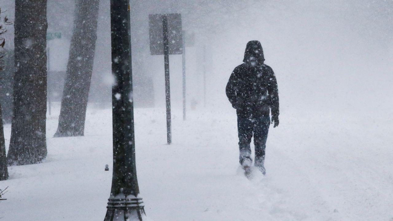 Un hombre lucha contra el viento y la nieve durante una tormenta en la costa de Jersey