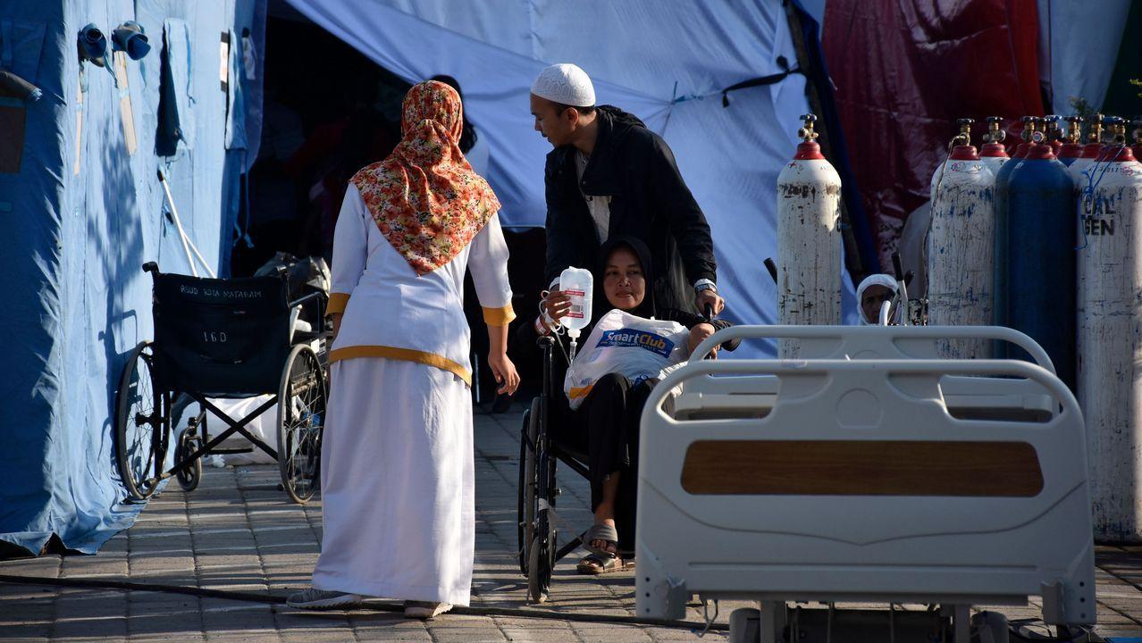Un hombre empuja a su esposa en una silla de ruedas en una sala de hospital improvisada en Mataram en la isla indonesia de Lombok.