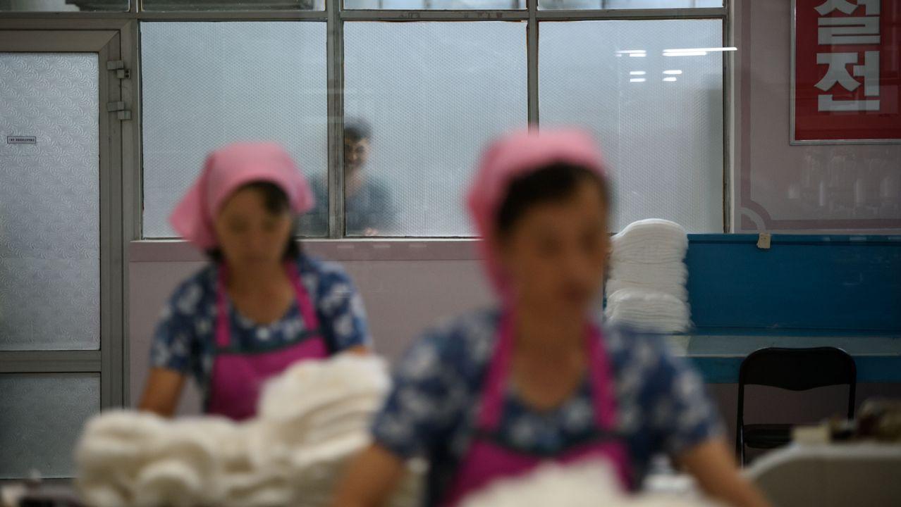 Un hombre mira a través de la ventana mientras varias trabajadoras realizan su tarea en Corea del Norte.