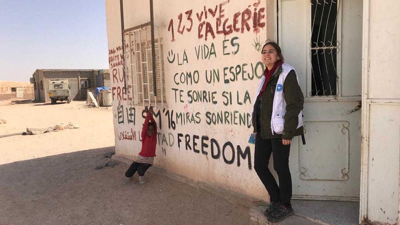 Maisa Ordóñez a la salida de una instalación médica mientras una niña refugiada juega cerca de ella