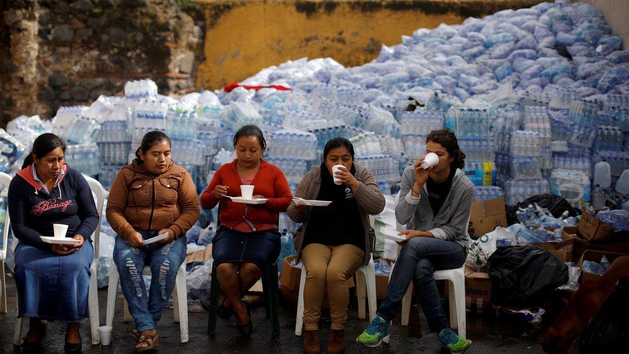 Un grupo de mujeres toman café en el área afectada por la erupción del volcán de Fuego, en Alotenango (Guatemala)
