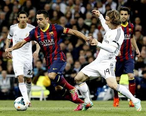 Xavi Hernández conduce la pelota presionado por Luca Modric en un clásico anterior.