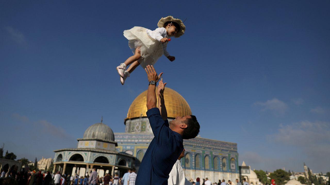 Un hombre palestino juega con su hijo, arrojándolo al aire, en Jerusalén