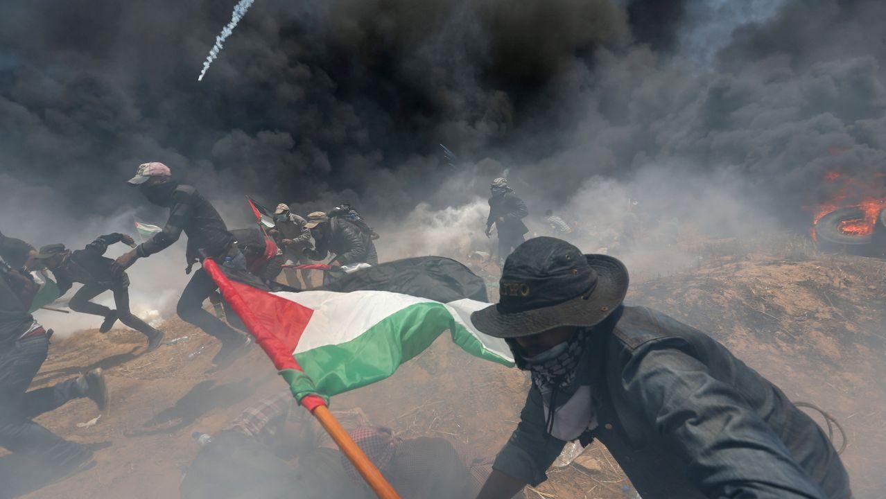 .Un grupo de manifestantes palestinos corren para protegerse del fuego israelí en Gaza