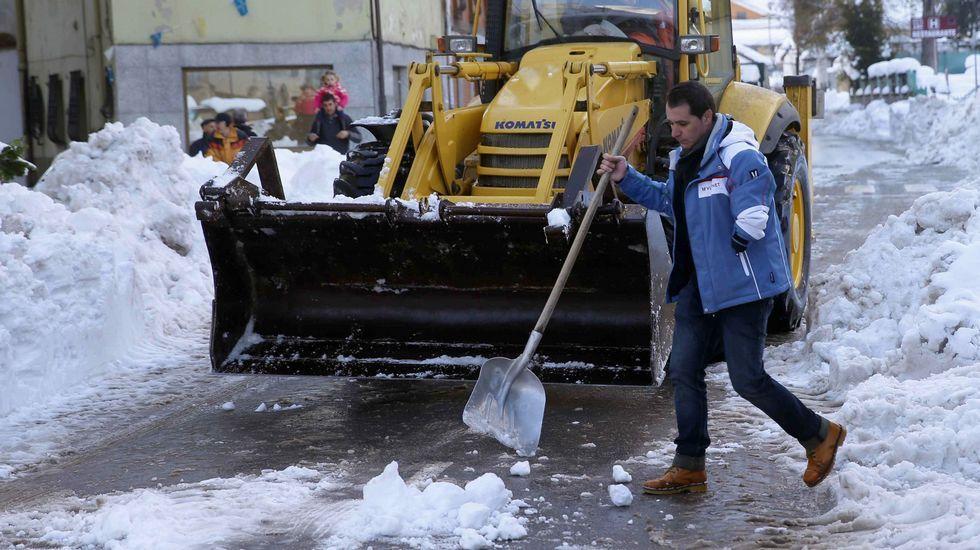Un hombre muestra el espesor de la nevada en Riofrío, en la vertiente asturiana de San Isidro.El alcalde del Concejo de Aller, David Moreno, durante la retirada de nieve en el pueblo de Felechosa.