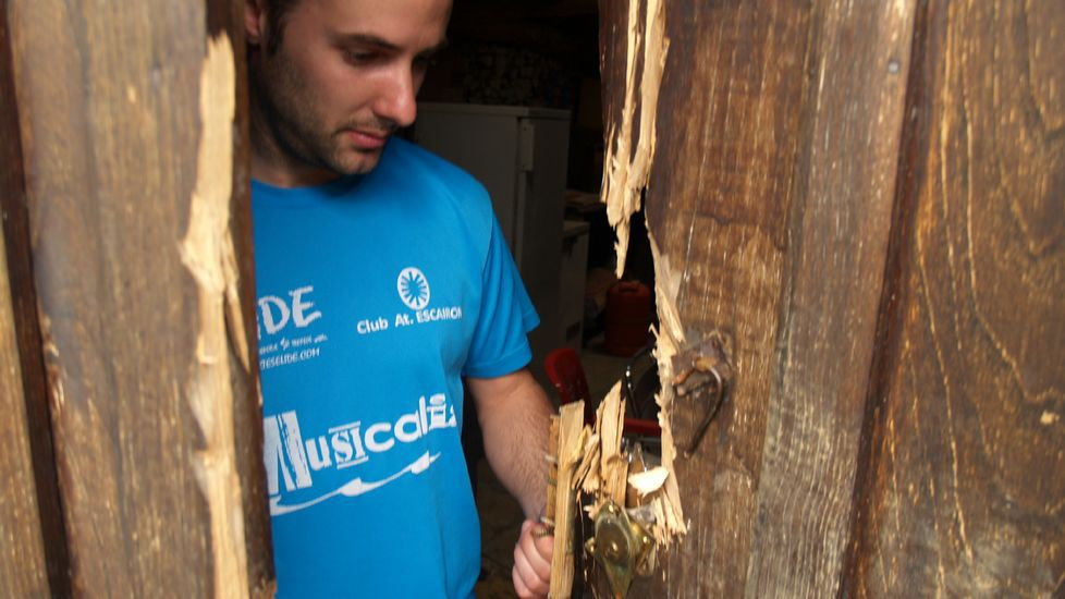 Destrozos en la puerta de una de las bodegas asaltadas en la parroquia de San Vitorio